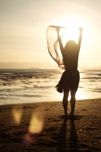 wsilhouette fo woman standing ont he beach in the sunset with her arms raised | You're Not Alone- I've reclaimed my voice | muchnessmama.com | victory escaping abuse
