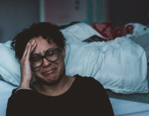 woman with short black hair and glasses sits next to bed crying | any abuser can cross the line into Physical abuse | muchnessmama.com
