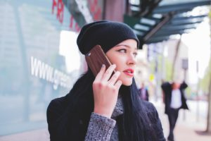 white woman with long dark hair standing on the sidewalk talking on her cell phone | getting help for domestic abuse | muchnessmama.com