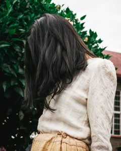a woman is staring at the ground with long dark hair covering her face | identifying the Mr. Right abuser |